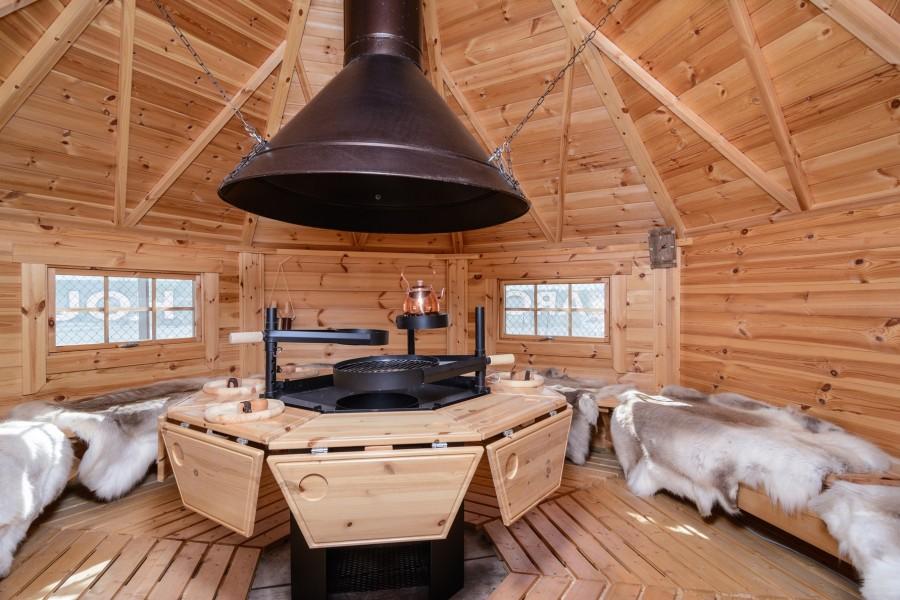 Innenbereich der Grillkota 12 m² mit verlängerten Tischen & Rentierfellen auf den Bänken