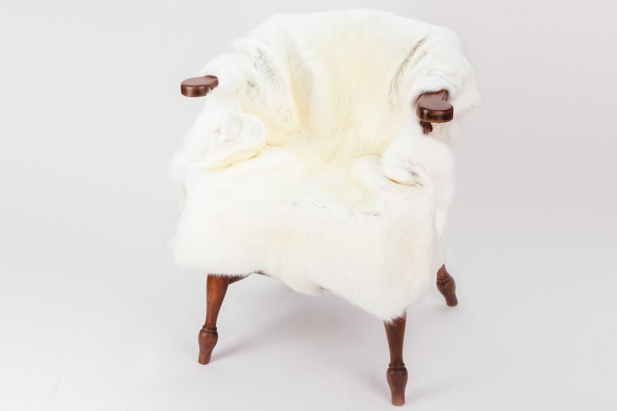 Weißes Rentierfell auf Holzstuhl