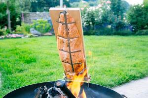 Feuerlachs mit Flammlachsbrett auf Feuerschalenrand